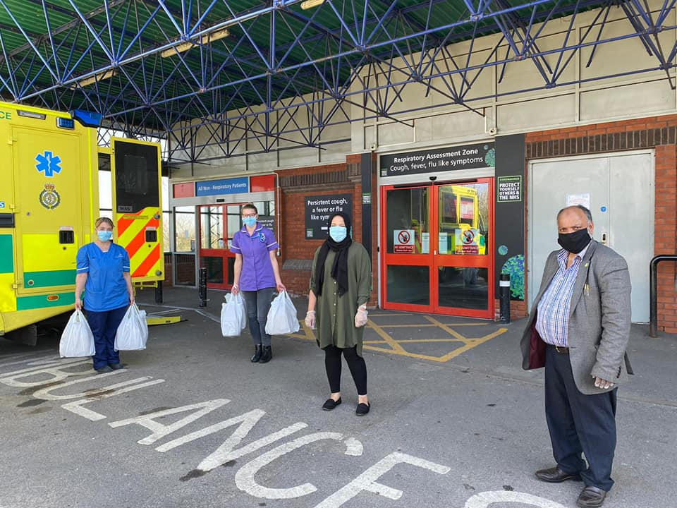 Two nurses and two people stood outside a hospital with food bags.